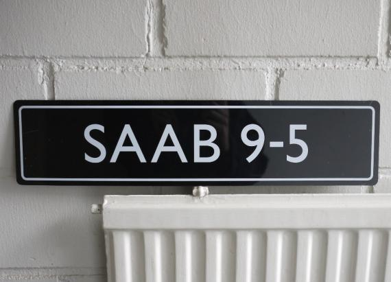 Muovinen kyltti SAAB 9-5 -tekstillä.